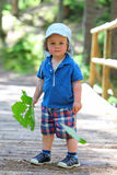 Portrait of a kid in forest, leaning against a Royalty Free Stock Photography