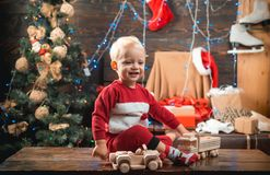 Portrait kid with gift on wooden background. Christmas kids - happiness concept. Cute little child girl is decorating stock photo