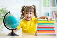 Portrait of kid girl considers Globe Stock Photo