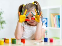 Portrait of kid girl with face and hands painted Stock Photo