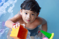 Portrait of a kid giving toys in a swimming pool Royalty Free Stock Image