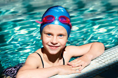 Portrait of a kid laughing in a swimming pool. Beautiful girl in a bathing suit, swim cap, goggles, holding on overboard in a swimming pool Royalty Free Stock Photography