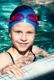 Portrait of a kid laughing in a swimming pool. Beautiful girl in a bathing suit, swim cap, goggles, holding on overboard in a swimming pool Royalty Free Stock Photos