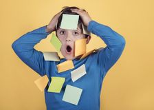 Portrait of kid with note papers stuck on body. On yellow background stock photos