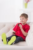 Portrait of kid sitting in white sofa. Royalty Free Stock Image