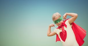 Portrait of kid wearing red cape and green mask showing muscles against clear sky Royalty Free Stock Images