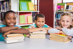 Portrait of kids in library. Portrait of kids leaning on books in library at school Royalty Free Stock Photo