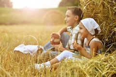 Portrait of kids with milk and fritters in field stock image