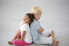 Portrait of kids sitting on the floor Stock Photos