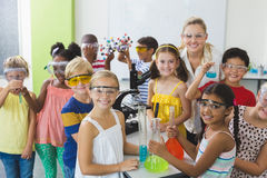 Portrait of kids and teacher standing in laboratory Stock Photo