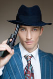 Portrait of a killer with a gun who backs up his hat. Portrait of a man in a business suit holding a gun in his hands royalty free stock images