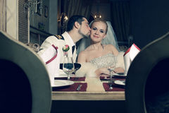 Portrait of kissing bride and groom sitting Stock Photography