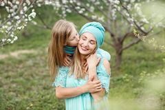 Portrait of kissing and happy mother and daughter in spring white garden. stock images
