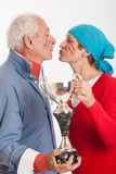 Kissing senior couple and french supporter. Portrait of a kissing Senior couple supporting french team with a trophy Stock Images