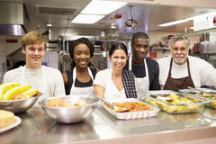 Portrait Of Kitchen Staff In Homeless Shelter. Behind Counter Smiling Royalty Free Stock Photo