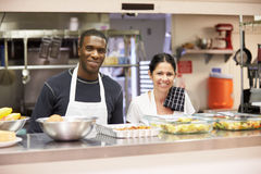Portrait Of Kitchen Staff In Homeless Shelter. Wearing Aprons Smiling At Camera Stock Images
