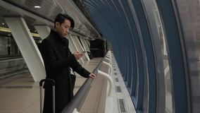 The portrait of korean man, who stands in the airport corridor and types messeges on his smartphone. The male with stylish haircut wears black coat and uses stock video footage