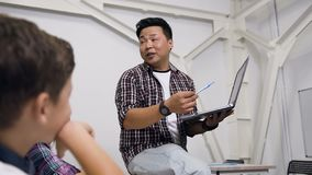Portrait of Korean teacher sitting on the desk with laptop in hand giving lesson for pupils. Pupils of primary school stock footage