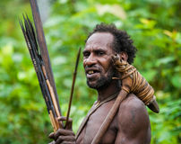 The Portrait Korowai man hunter with arrow and bow. Tribe of Korowai Kombai , Kolufo. Royalty Free Stock Photos