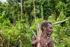 The Portrait Korowai man hunter with arrow and bow. Tribe of Korowai (Kombai , Kolufo). Royalty Free Stock Images