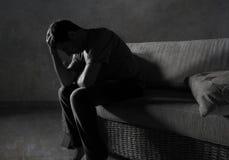 Portrait léger dramatique de mode de vie du jeune homme triste et déprimé s'asseyant au divan à la maison louche dans l'effort de photos stock