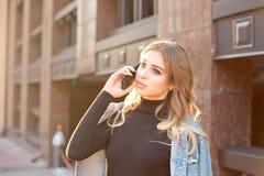 Portrait ?l?gant ?motif d'une jeune femme blonde sur un plan rapproch? de fond de paysage urbain dans le coucher de soleil image stock