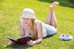 Portrait of l woman lying on green lawn in park and reading book Royalty Free Stock Photos