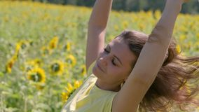Portrait La belle femme avec de longs cheveux détend la position dans un domaine avec des tournesols cheveux déchirant dans le ve banque de vidéos