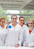 Portrait of lab partners posing with a flask Stock Photography