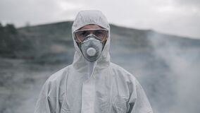 Portrait of a laboratory assistant in a mask coming out of poisonous smoke