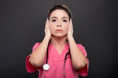 Portrait of lady doctor covering ears like not hearing. Or deaf concept on black background royalty free stock photos