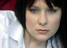 Portrait of a lady, redhead, blue eyes. Portrait of a lady with a nose ring, intense stare Stock Image