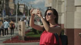 The portrait of lady tourist who takes photos on her smartphone on the vibrant street in sunny day. stock video