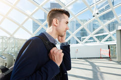 Portrait latéral d'homme sérieux à l'appel téléphonique de téléphone portable avec le sac à dos Photo libre de droits