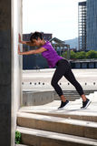 Portrait latéral de femme de couleur étirant la routine de séance d'entraînement dehors photos libres de droits