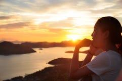 Portrait latéral de fille faisant le phonecall quand coucher du soleil Photo stock