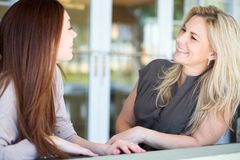 Two women taling and laughing. Stock Photos