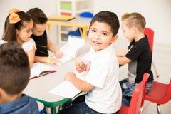 Preschool student enjoying class. Portrait of a Latin preschool pupil working on a writing assigment and enjoying school stock photography