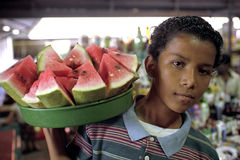 Portrait of Latino boy selling water melons. Nicaragua, city, capital, Managua: A boy carries pieces water melons on his shoulder. He sells the melon in and Royalty Free Stock Image