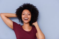 Laughing african american woman with hands in curly hair on gray background. Portrait of laughing african american woman with hands in curly hair on gray royalty free stock image