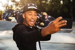 Portrait of a laughing african male teenager taking a selfie. While holding a skateboard on his shoulders outdoors Stock Photos