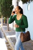 Laughing asian woman walking outside on street and talking on cell phone Stock Photography