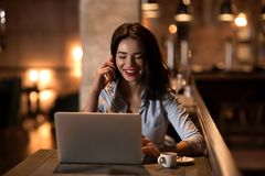 Portrait of laughing and beautiful businesswoman speaking on the phone and working on her laptop in modern restaurant. The Portrait of laughing and beautiful Royalty Free Stock Image