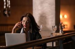 Portrait of laughing and beautiful businesswoman speaking on the phone and working on her laptop in modern restaurant. The Portrait of laughing and beautiful Royalty Free Stock Photos