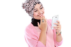 Portrait of a laughing beautiful muslim woman texting with her s Royalty Free Stock Images