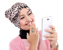 Portrait of a laughing beautiful muslim woman texting with her s Royalty Free Stock Photography