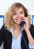 Portrait of laughing blond businesswoman at office at phone Stock Photography