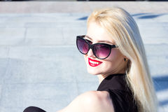 Portrait of a laughing blond woman with red lips in sunglasses Stock Photo