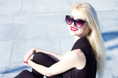 Portrait of a laughing blond woman with red lips in sunglasses Royalty Free Stock Photos