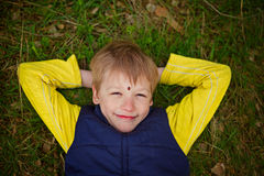 Portrait of the laughing boy which lies on a grass with ladybug Royalty Free Stock Photography